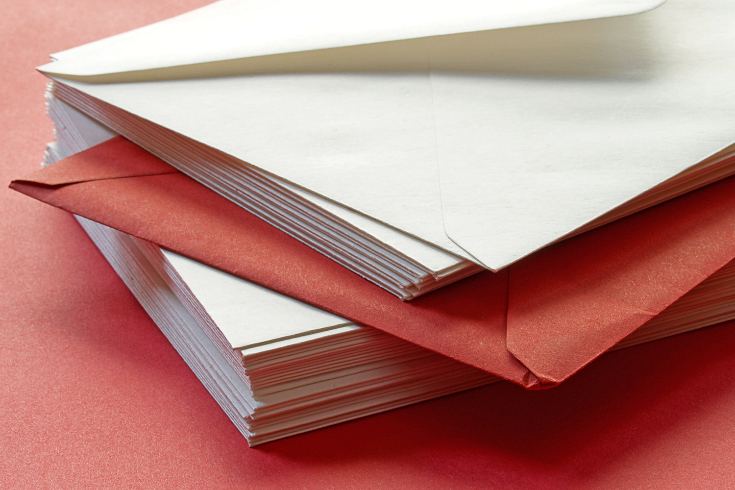 A stacked pile of post mail on a red table to represent charity response handling