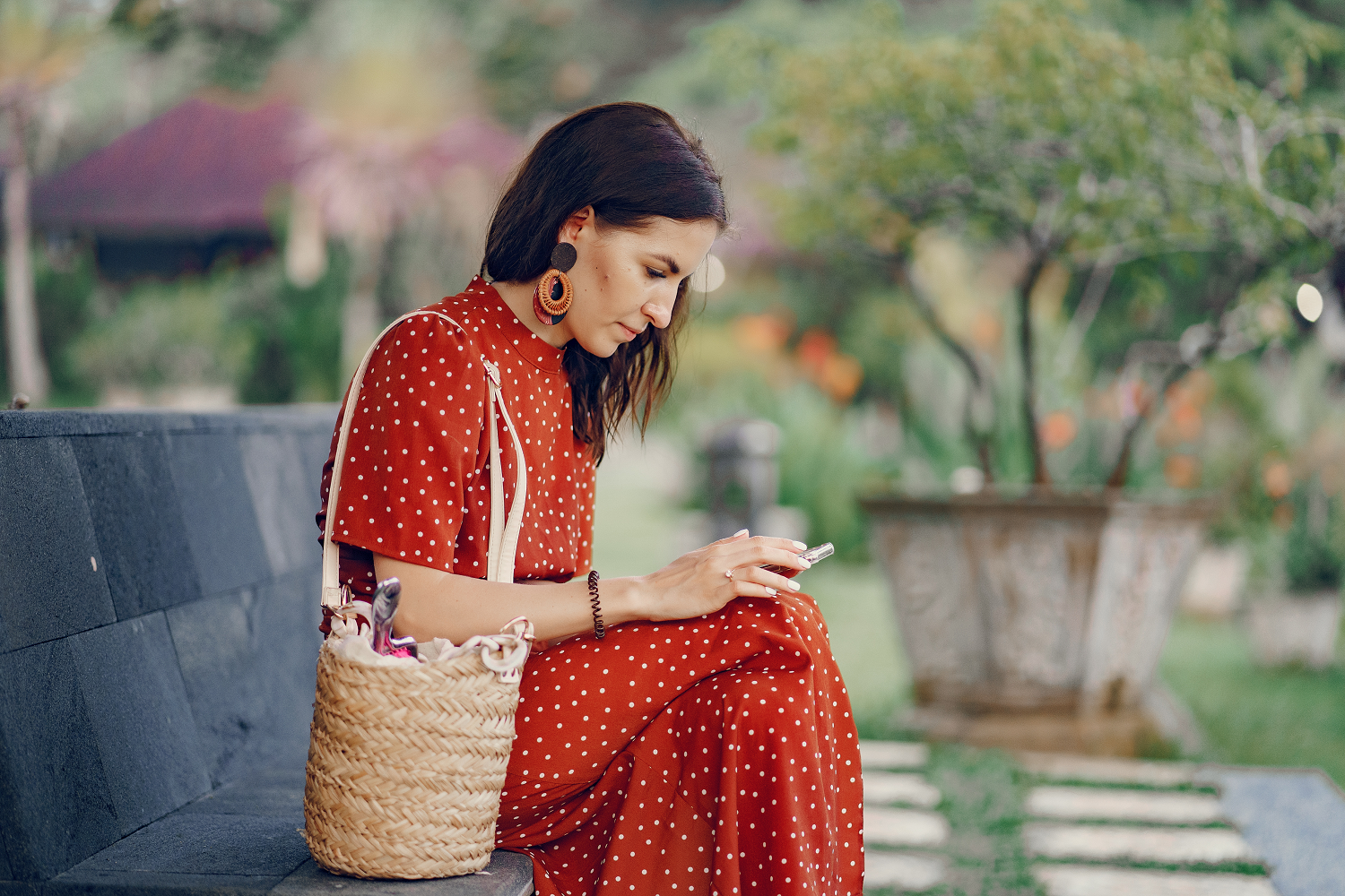 Woman in red dress using smartphone on bench, as part of charity response handling (1)